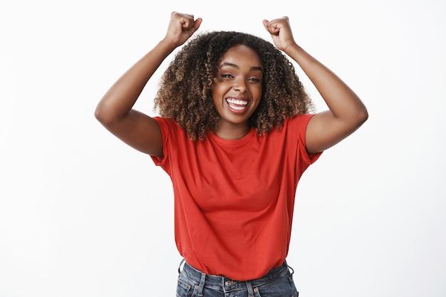 Excitada e despreocupada feliz celebrando mulher de pele escura levantando as mãos de felicidade e vitória sorrindo amplamente sentindo o gosto do sucesso e triunfo sobre a parede branca