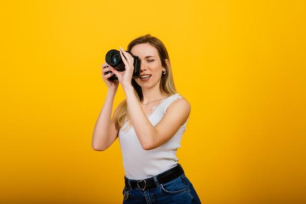Excitada fotógrafa trabalhando em estúdio. retrato de uma menina loira deslumbrante com câmera fotográfica.