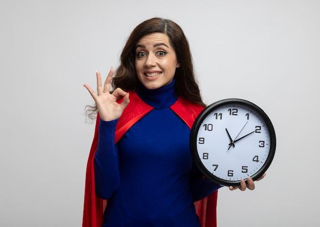 Excitada garota super-heroína caucasiana com capa vermelha faz gestos com a mão ok e segura relógio isolado na parede branca com espaço de cópia