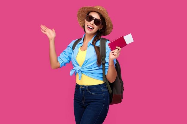Excitada turista feminina, segurando o passaporte e bilhetes de viagem sobre fundo rosa isolado. estudante mulher com roupas casuais de verão. mulher caucasiana sorridente em óculos de sol.