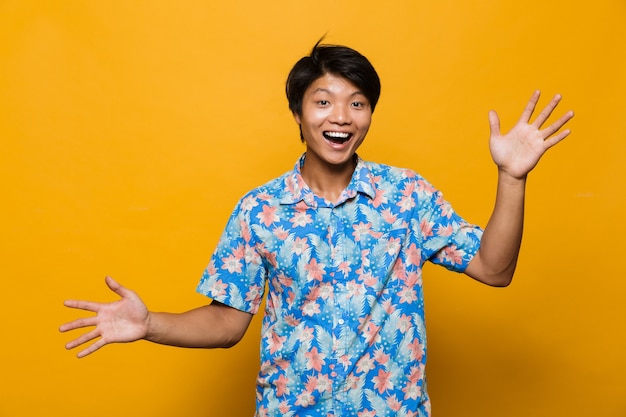 Excitado emocional jovem asiático posando isolado sobre o espaço amarelo.