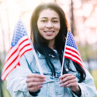Excitado, étnico, mulher, com, lembrança, bandeiras americanas