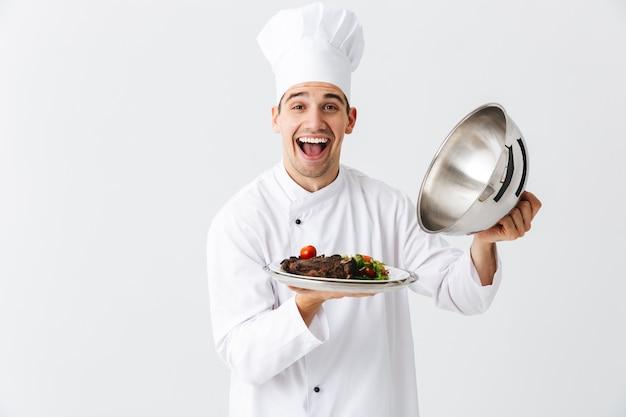 Excitado homem chef cozinheiro usando capa uniforme de abertura cloche isolada na parede branca, mostrando prato de carne