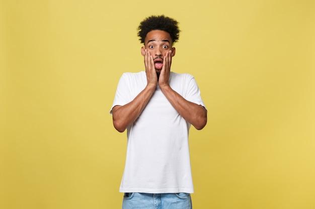 Excitado jovem homem afro-americano em choque e perplexidade, segurando as mãos na cabeça