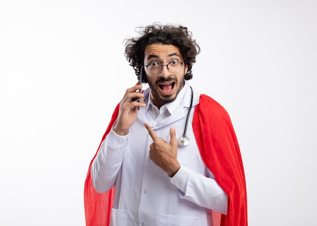 Excitado jovem super-herói caucasiano com óculos ópticos, uniforme de médico com capa vermelha e estetoscópio no pescoço, apontando e falando ao telefone isolado na parede branca