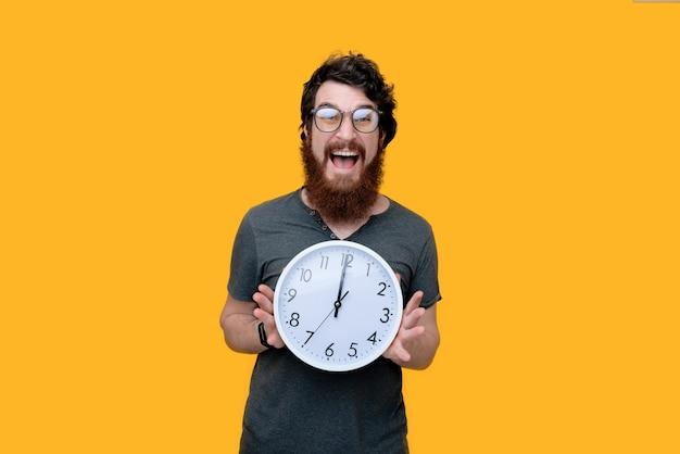 Excitd barbudo cara com galsses, segurando um relógio, parado no amarelo