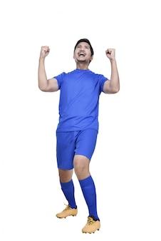 Excited asian male footballer posing comemorar