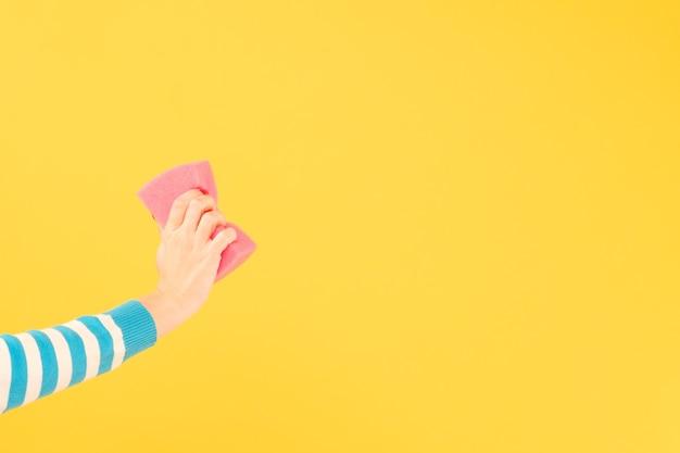 Exclua o conceito. mão de uma mulher apagando informações imaginárias com a esponja. copie o espaço em fundo amarelo.
