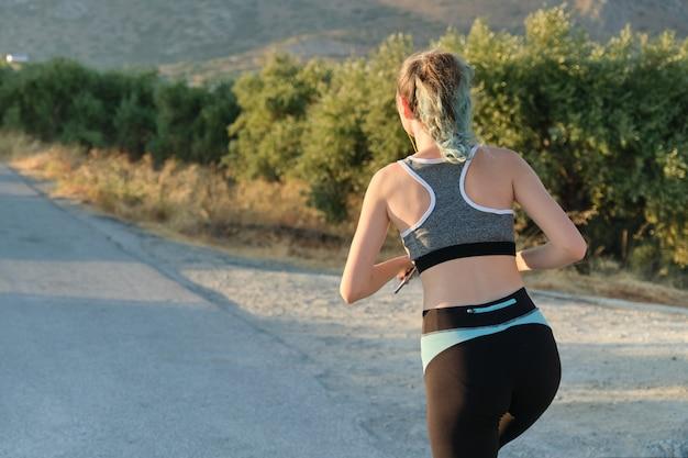 Executando a garota fitness, estrada nas montanhas, vista traseira, copie o espaço