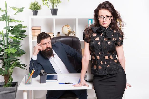 Executando o escritório com sucesso. funcionários de escritório. proprietário da empresa e secretária do escritório. mulher sexy e homem barbudo em roupas de escritório. assistente feminino sensual em pé na mesa do chefe.