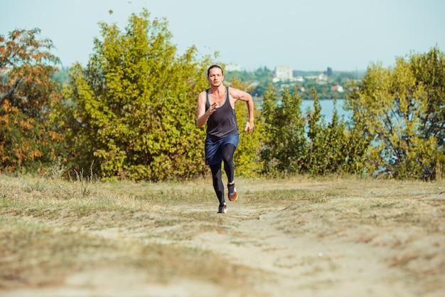 Executando o esporte. corredor de homem correndo ao ar livre na natureza cênica. ajuste a trilha de treinamento do atleta masculino musculoso correndo para a maratona. desportivo cabe homem atlético malhando em roupas de compressão em sprint