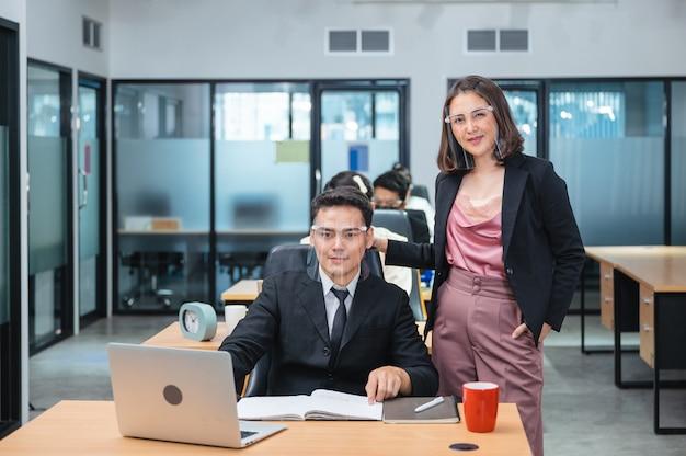Executiva asiática com funcionário do sexo masculino na mesa usando protetor facial para coronavírus protetor, covid-19 em novo escritório normal