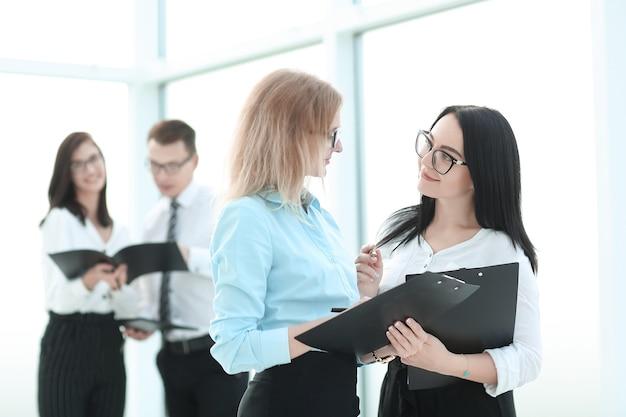 Executiva, assinando um documento comercial, em pé no escritório