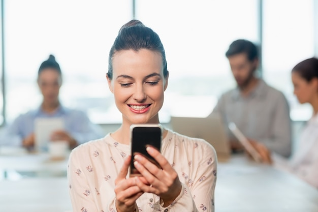 Executiva de negócios usando seu telefone celular na sala de conferências