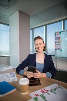 Executiva de negócios usando seu telefone celular no escritório