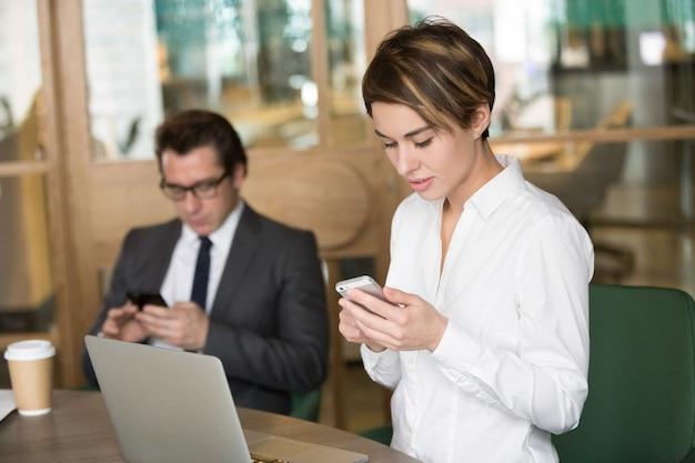 Executiva, e, homem negócios, usando, telefones móveis, para, trabalho, em, escritório