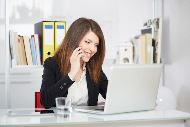 Executiva, falando, para, móvel, e, trabalhando, em, escritório, com, laptop