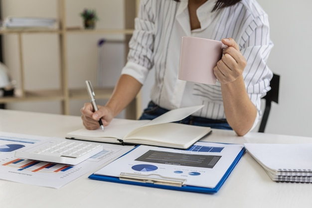 Executiva, fazendo anotações em um caderno e tomando café, verifica vendas de produtos e documentos financeiros, é executiva de uma startup. conceito de administração de empresas.
