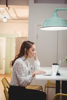 Executiva feminina falando no celular enquanto usa tablet digital