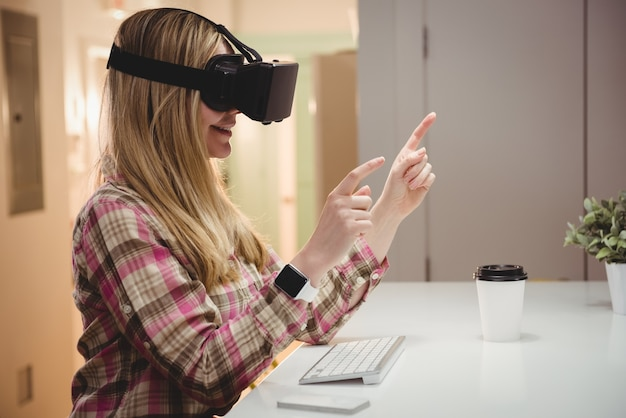Executiva feminina usando fone de ouvido de realidade virtual no escritório