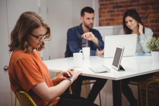 Executiva feminina usando smartwatch enquanto colegas discutem no laptop