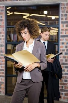 Executiva, ficar, perto, biblioteca, e, olhar, documentos