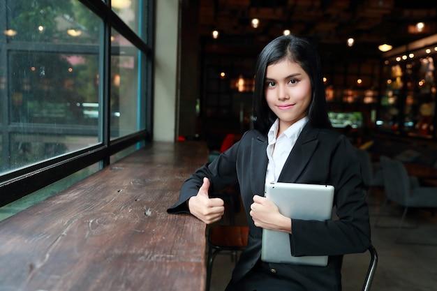 Executiva, mostrando, polegar cima, e, símbolo vitória, ligado, dela, mãos, para, significado, sucesso, projeto, com, notas banco, e, computador, ligado, tabela