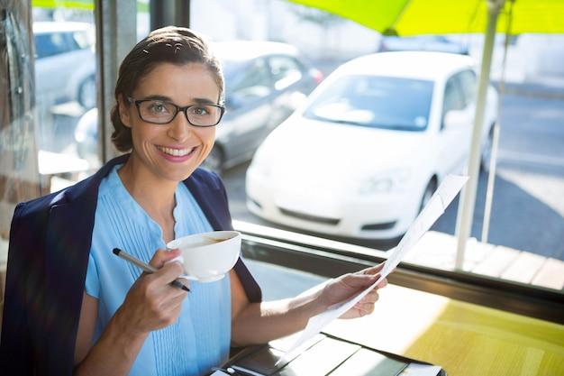 Executiva olhando um documento enquanto toma um café