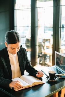 Executiva, olhar, em, diário, sobre, escrivaninha