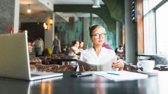 Executiva, segurando, jornal, sentando, em, restaurante