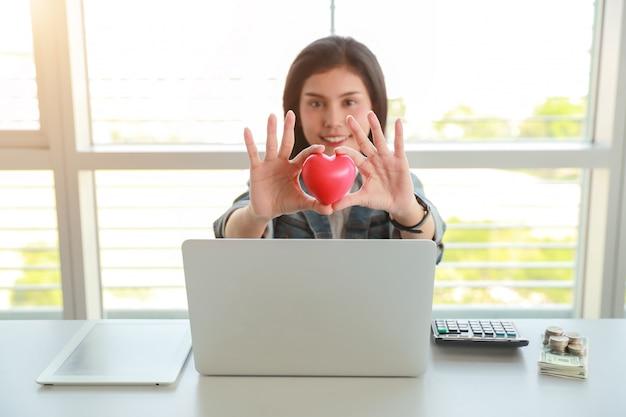 Executiva, segurando, vermelho, coração, símbolo, ligado, tabela, com, computador