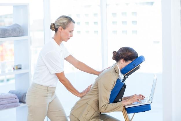 Executiva, tendo, costas, massagem, enquanto, usando, dela, laptop, em, escritório médico