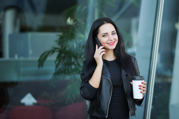 Executiva, usando, digital, smartphone, e, bebida, café, perto, ao lado, escritório, predios