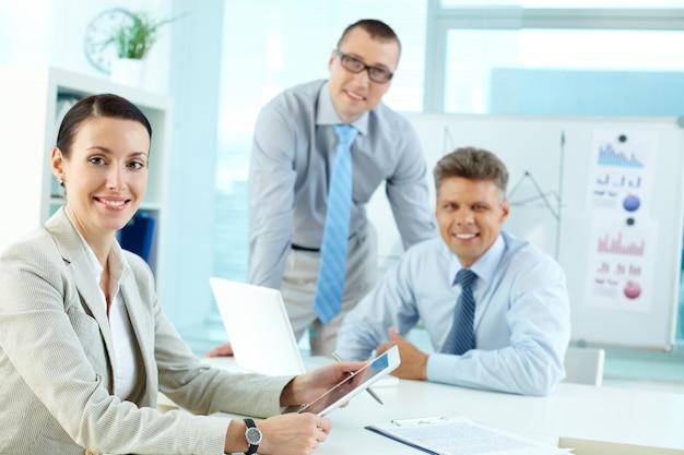 Executivo alegre com colegas de trabalho de fundo
