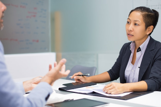 Executivo asiático novo sério que escuta o empregado do sexo masculino