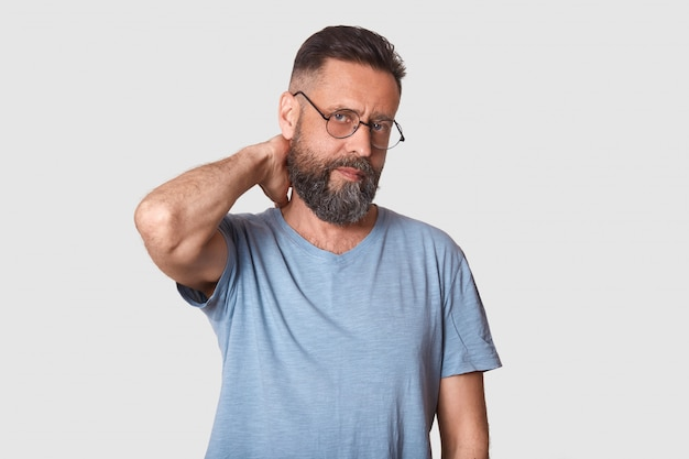 Executivo bonito sem emoção cansado olha firmemente para a câmera, segurando o braço para trás, fazendo massagem no pescoço após um árduo dia de trabalho