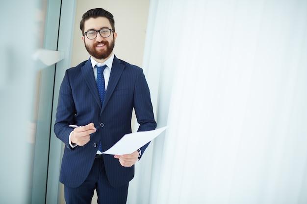 Executivo com óculos segurando contrato e caneta
