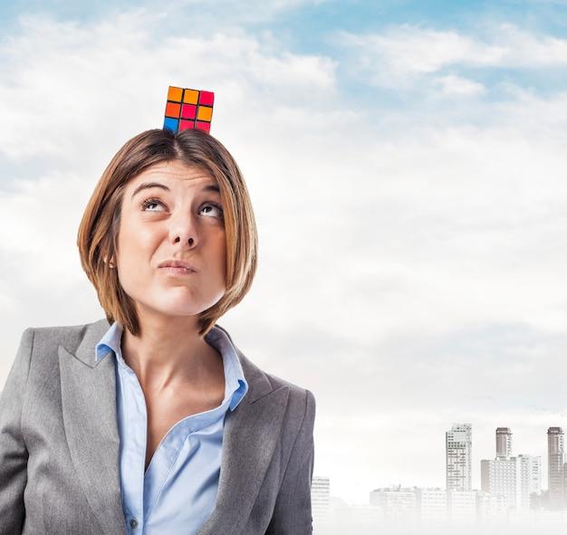 Executivo com um cubo mágico em sua cabeça e olhando para cima