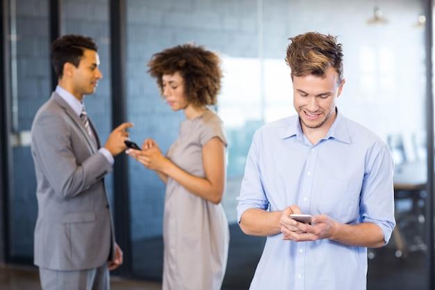 Executivo confiante usando telefone celular com seus colegas de trabalho