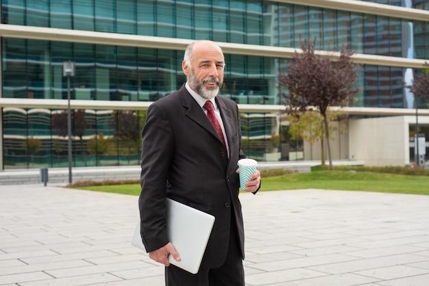 Executivo de cabelos cinzento confiante feliz com laptop