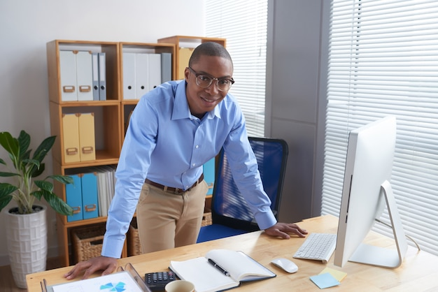 Executivo de negócios alegre, apoiando-se na mesa do chefe