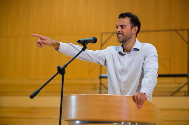 Executivo de negócios apontando enquanto faz um discurso no centro de conferências