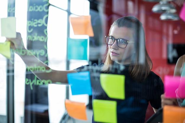 Executivo de negócios, colando notas autoadesivas no vidro