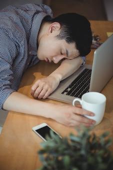Executivo de negócios, dormindo em sua mesa