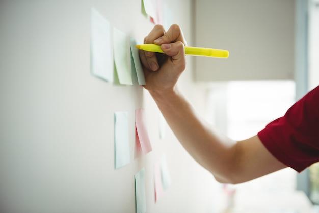 Executivo de negócios, escrevendo em notas autoadesivas