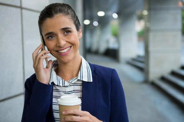 Executivo de negócios falando no celular enquanto toma um café