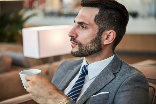 Executivo de negócios imerso em pensamentos com um pouco de café