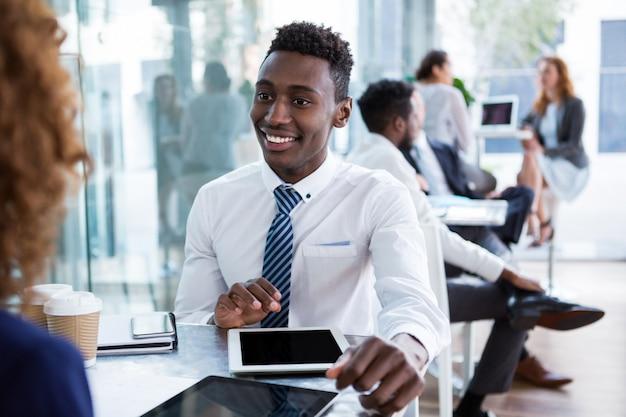 Executivo de negócios interagindo enquanto estiver usando tablet digital no escritório