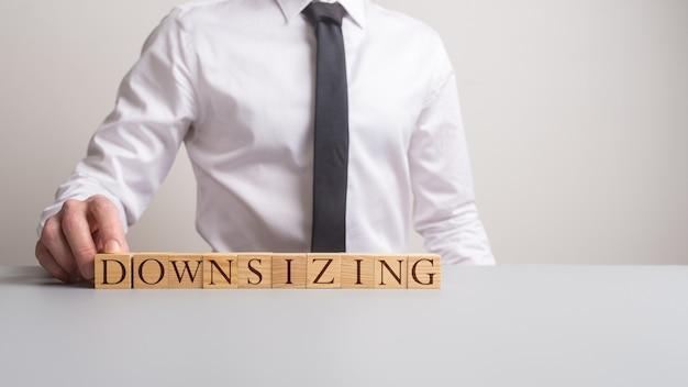 Executivo de negócios sentado em sua mesa de escritório com o downsizing do sinal na frente dele em uma imagem conceitual.