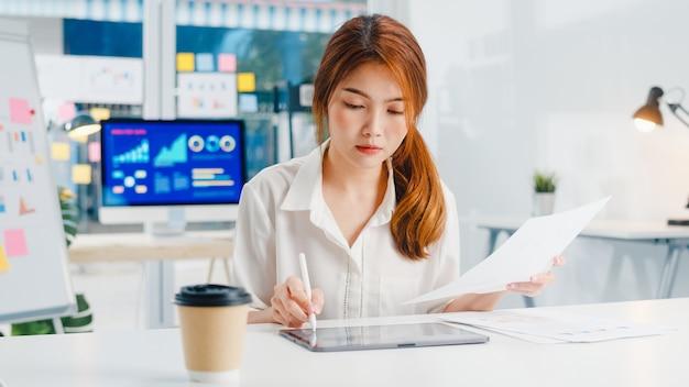 Executivo de sucesso ásia jovem empresária smart casual wear desenhando, escrevendo e usando a caneta com computador tablet digital pensando em ideias de busca de inspiração processo de trabalho em um escritório em casa moderno.